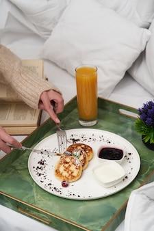 Livre de lecture de femme tout en prenant son petit déjeuner au lit. femme, dans, peignoir, petit déjeuner, dans, lit hôtel, gros plan