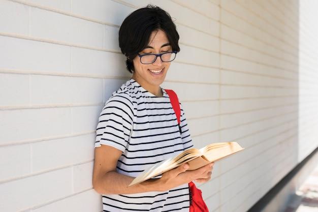 Livre de lecture d'homme asiatique souriant
