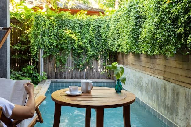 Livre de lecture de l'homme au bord de la piscine avec une tasse de café avec des plantes en arrière-plan.