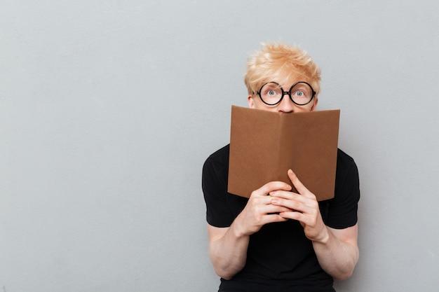 Livre de lecture homme caucasien choqué.