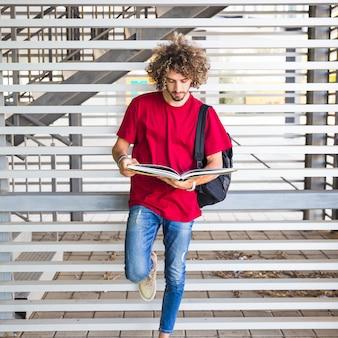 Livre de lecture jeune étudiant près du mur