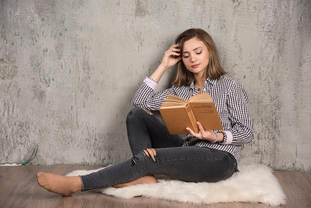 Livre De Lecture Jeune étudiant Soigneusement Sur Mur De Pierre Photo gratuit