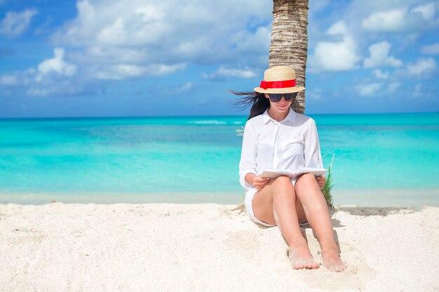 Livre de lecture de jeune femme au cours de la plage blanche tropicale