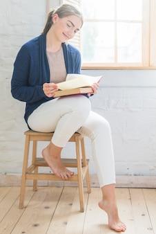 Livre de lecture de jeune femme souriante