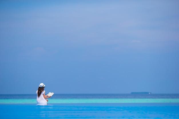 Livre de lecture de jeune fille près de la piscine