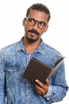 Livre de lecture de jeune homme indien tout en pensant isolé