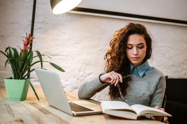 Livre de lecture jolie femme brune au bureau à la maison.