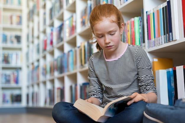 Livre de lecture de jolie fille dans la bibliothèque