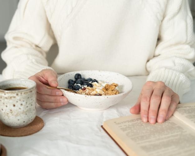 Livre de lecture et manger un petit-déjeuner d'hiver de vacances saines avec du muesli granola et du yaourt dans un bol sur la table blanche. repas bio du matin à l'avoine