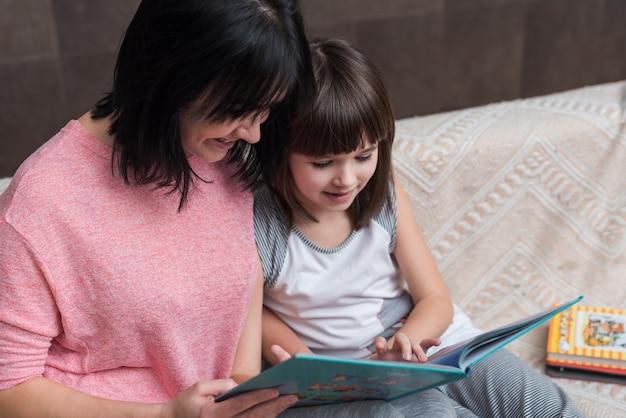 Livre lecture mère et fille sur divan