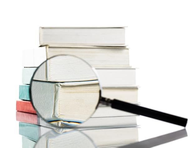 Livre et loupe isolés sur blanc. concept de recherche