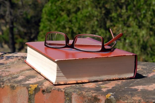 Livre et lunettes sur le mur en plein air
