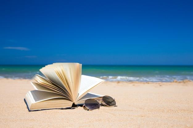 Livre et lunettes de soleil sur la plage tropicale
