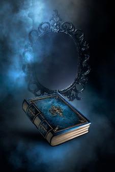 Livre magique de fantaisie vintage sur fond sombre, miroir magique de prédictions et de divination, fumée, brouillard, clair de lune néon dans l'obscurité. illustration 3d.