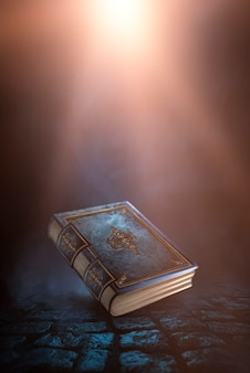 Livre magique de fantaisie vintage sur fond sombre, paysage, fumée, brouillard, clair de lune néon dans l'obscurité. illustration 3d.