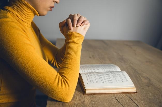 Livre de main de femme en prière dans une pièce sombre