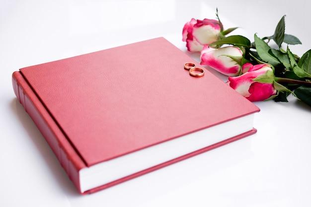Livre de mariage ou album couvert de cuir rouge avec deux alliances et trois roses