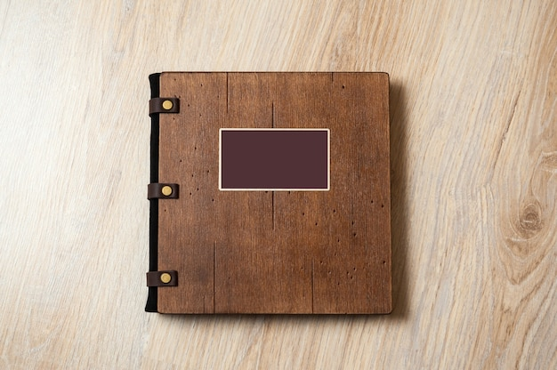 Livre de mariage avec une couverture en bois sur une texture en bois.