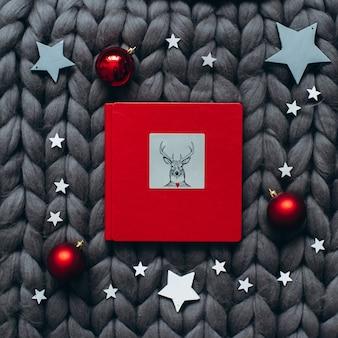 Livre de noël rouge avec des boules dans la couverture tricotée grise