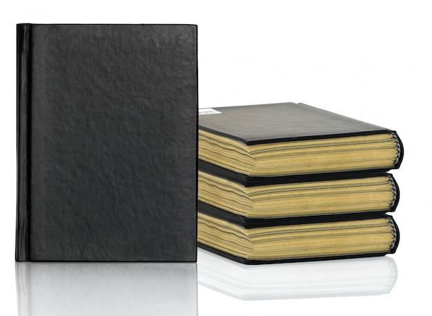 Livre noir pose avec ombre sur fond blanc