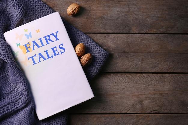 Un livre, des noix et une couverture de laine sur bois