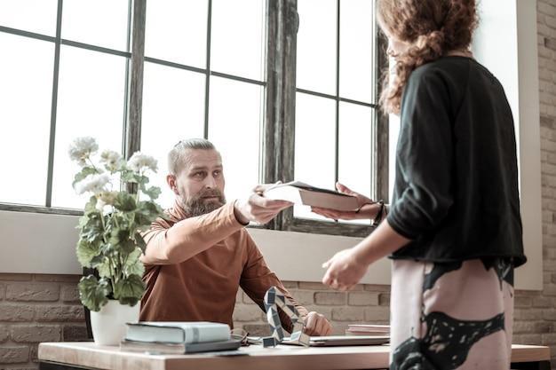 Livre à offrir. thérapeute barbu portant un col polo orange donnant un livre à une adolescente après la thérapie