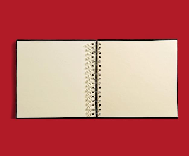 Livre d'ordre ouvert à reliure spirale avec des pages vierges non lignées pour vos notes ou calendrier sur rouge
