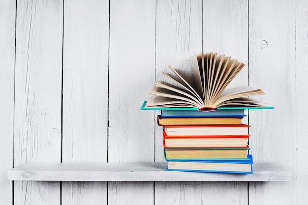 Le livre ouvert sur d'autres livres multicolores. sur une étagère en bois. un fond blanc en bois.