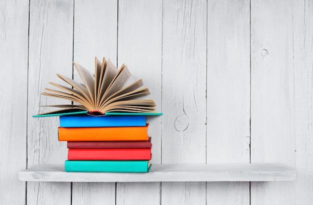 Le livre ouvert et autres livres multicolores. sur une étagère en bois. une table blanche en bois.