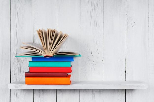 Le livre ouvert sur d'autres livres multicolores.