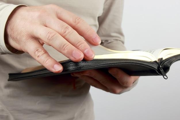 Livre ouvert la bible entre les mains des hommes