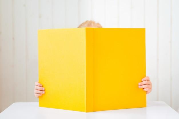 Livre ouvert cachant le visage de la lecture petite fille.