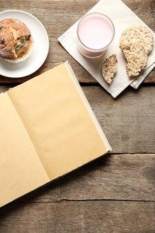 Livre ouvert et collation sur fond de table en bois