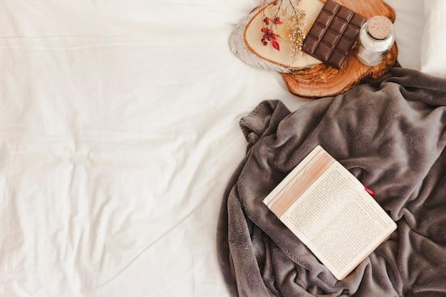 Livre ouvert et couverture près de la barre de chocolat