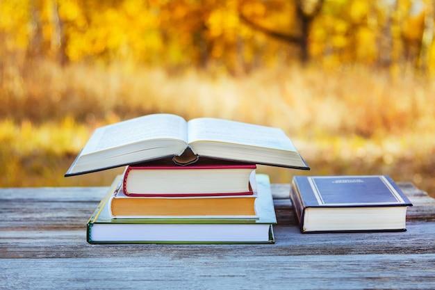 Livre ouvert dans une pile de livres sur une table dans un parc d'automne.