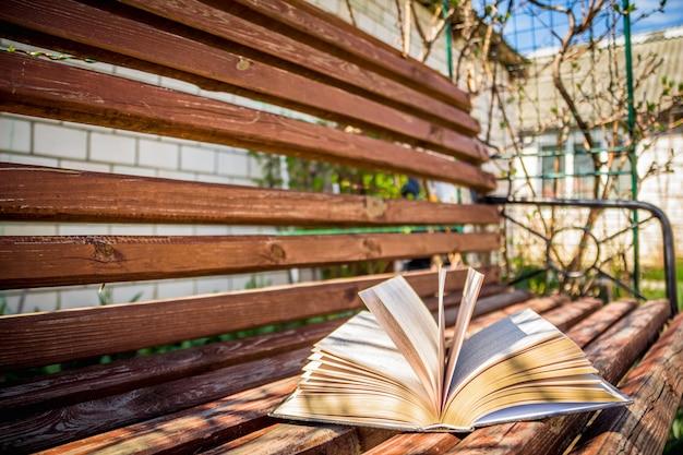 Livre ouvert épais posé dans la cour sur le banc
