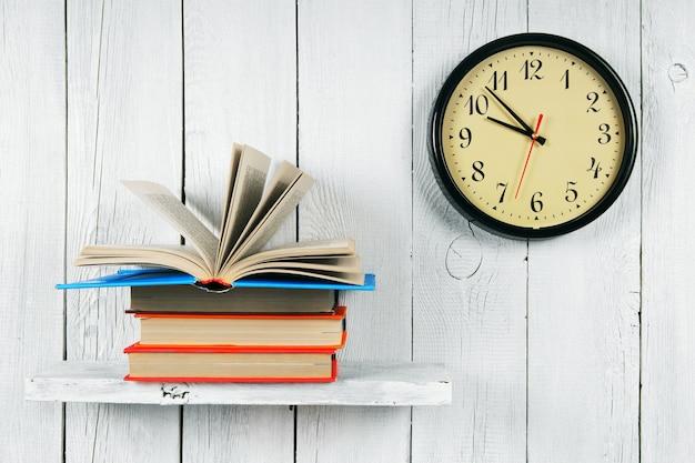 Livre ouvert sur une étagère en bois et montres. sur un fond en bois blanc.