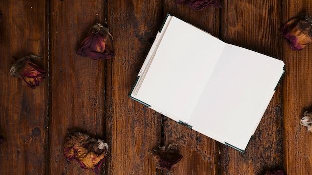 Livre ouvert avec des fleurs séchées sur fond en bois