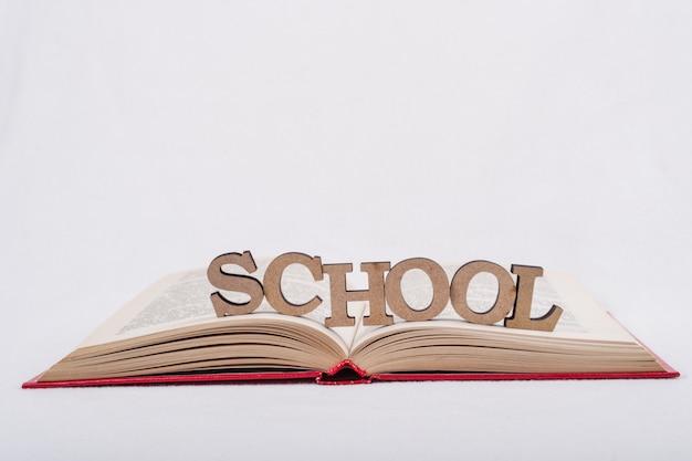 Livre ouvert sur fond blanc. école de mot lettres abstraites en bois