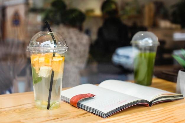 Livre ouvert et jus de fruits frais au café