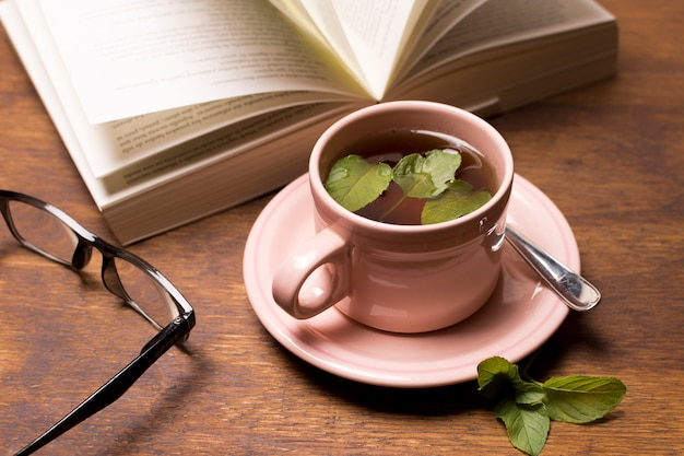 Un livre ouvert et des lunettes de vue avec une tisane verte dans une tasse rose sur une table en bois