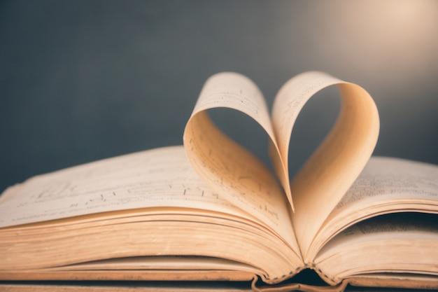 Livre ouvert avec une page en forme de coeur.