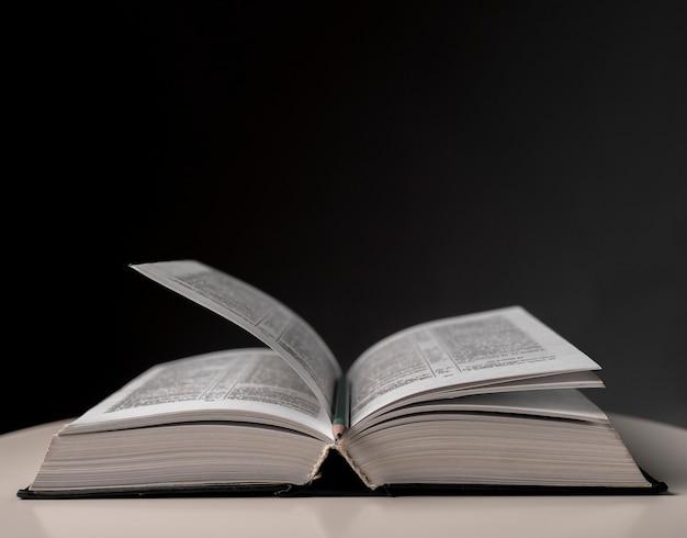 Livre ouvert avec page tournante. manuel en couverture rigide sur table.