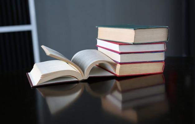 Livre ouvert et pile de livres à couverture rigide sur une table en bois.