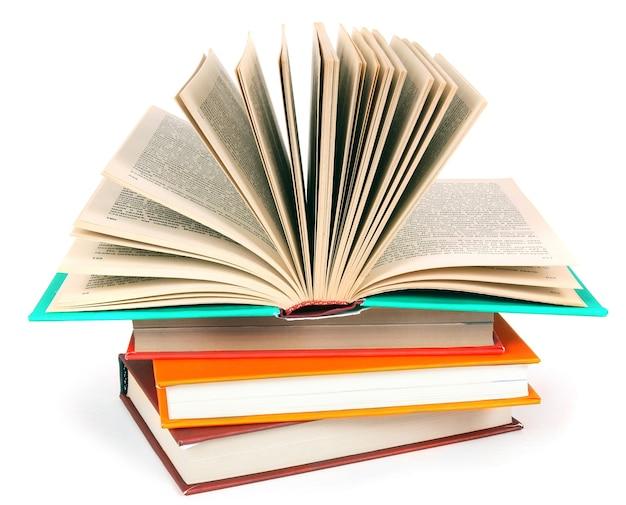 Livre ouvert sur une pile de livres multicolores sur blanc.