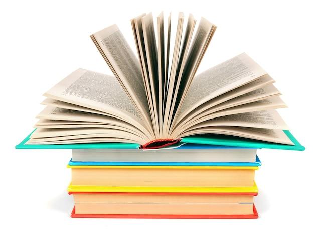 Le livre ouvert sur une pile de livres multicolores.