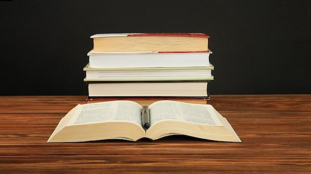Livre ouvert sur une pile de livres sur une table.
