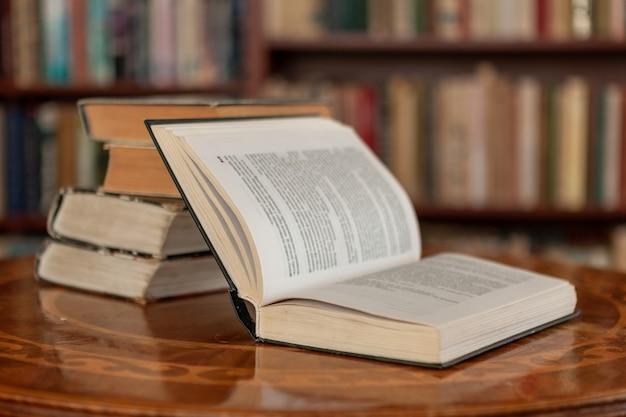 Livre ouvert et pile de vieux livres dans le contexte de la bibliothèque à domicile