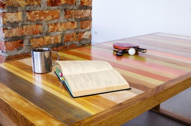 Livre ouvert et une raquette de ping-pong, allongé sur une table en bois