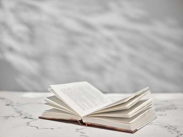 Livre ouvert sur table blanche